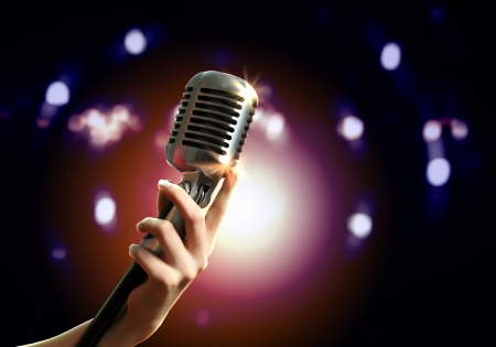 Female hand holding a single retro microphone against colourful background Stock Photo - 17399748