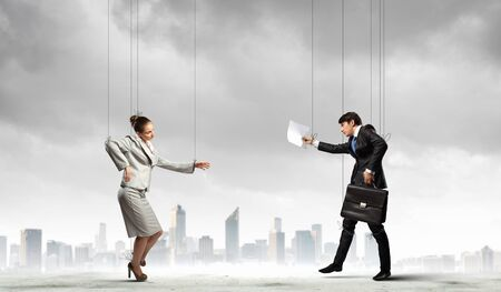 Image of businesspeople hanging on strings like marionettes against city background  Conceptual photography photo