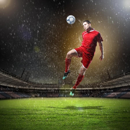 football stadium: football player in red shirt striking the ball at the stadium under rain