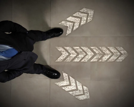 Top view of businessman standing against directions background Stock Photo - 17400664