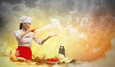 Asian female cooking with magic against color background Stock Photo - 17400089