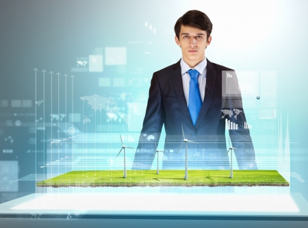 Image of young businessman looking at high-tech picture of windmills photo