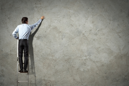 businessman standing on ladder drawing diagrams and graphs Stock Photo - 17400821