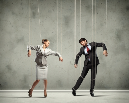to obey: Image of businesspeople hanging on strings like marionettes  Conceptual photography Stock Photo