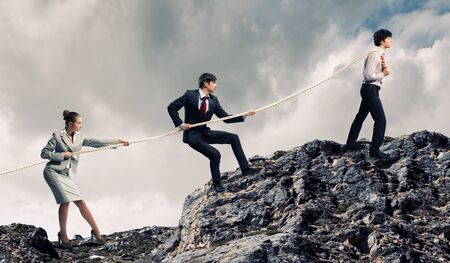 pulling rope: Image of three businesspeople pulling rope atop of mountain Stock Photo