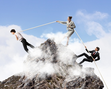 Image of three businesspeople pulling rope atop of mountain photo
