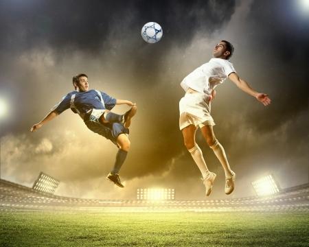 deux joueurs de football de saut pour frapper la balle dans le stade