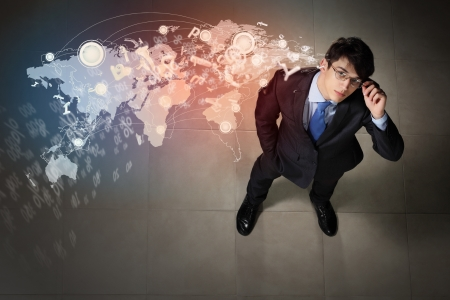 Top view of young businessman making decision against global network back photo