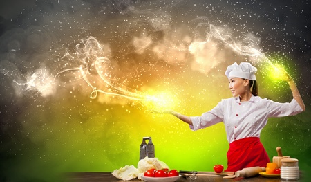 Asian female cooking with magic against color background Stock Photo - 17400126