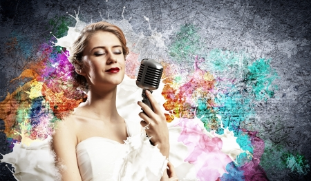 Image of female blonde singer holding microphone against color background with closed eyes photo