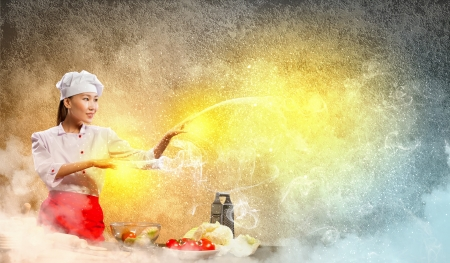 Asian female cooking with magic against color background Stock Photo - 17400876