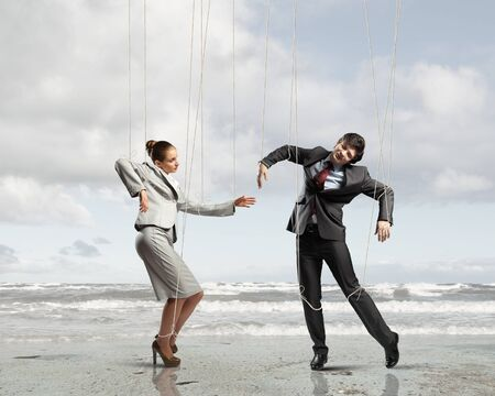 Image of businesspeople hanging on strings like marionettes against sea background  Conceptual photography photo