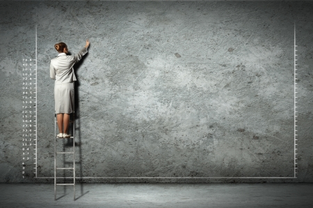 businesswoman standing on ladder drawing diagrams and graphs on wall photo