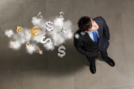 pound sign: Top view of young businessman making decision currency signs in air Stock Photo