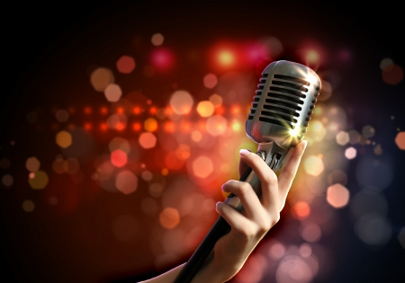live music: Female hand holding a single retro microphone against colourful background