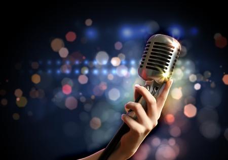 live entertainment: Mano femminile in possesso di un singolo microfono retr� su sfondo colorato Archivio Fotografico