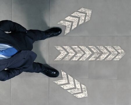 Top view of businessman standing against directions background Stock Photo - 17431027