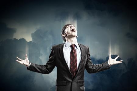 amok: biznesmen w złości krzyczy przeciwko pochmurne tle