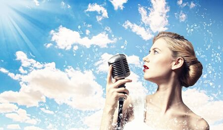 Image of female blonde singer holding microphone against clouds background photo
