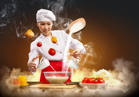 Asian female cooking with magic against color background photo