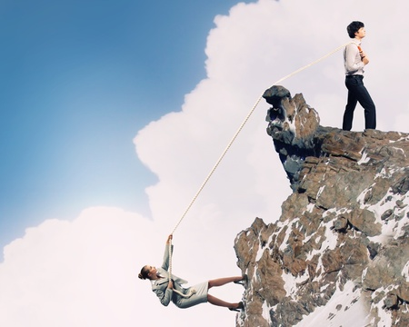 Image of busionessman and businesswoman pulling rope atop of mountain Stock Photo