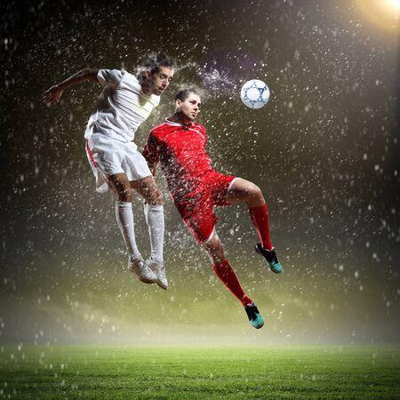 dos jugadores de f�tbol en salto para golpear la pelota en el estadio Foto de archivo - 17430828