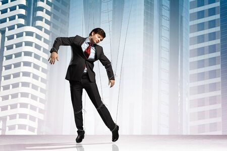 Image of businessman hanging on strings like marionette against city background  Conceptual photography Stock Photo - 17428767