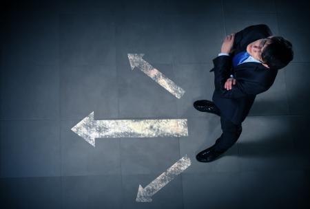 toma de decision: Vista superior de negocios de pie contra el fondo direcciones Foto de archivo