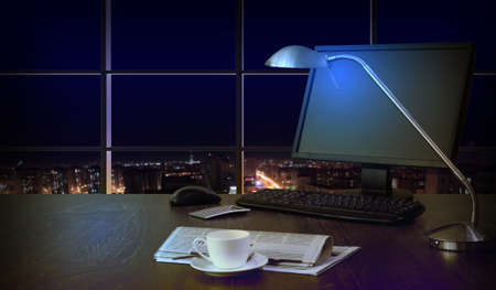 Work place in the office at night with a city view from window Stock Photo - 17450704