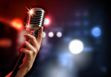 zábava: Ženská ruka drží jeden retro mikrofon proti barevné pozadí Reklamní fotografie