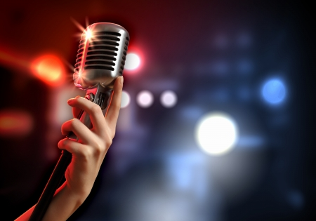 Vrouwelijke hand die een retro microfoon tegen kleurrijke achtergrond Stockfoto