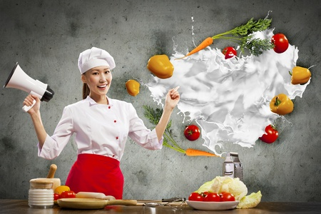 Asian female cook holding megaphone vegetables flying in air Stock Photo - 17494707