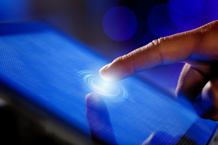 Closeup of finger touching blue toned screen on tablet-pc Stock Photo - 17494844
