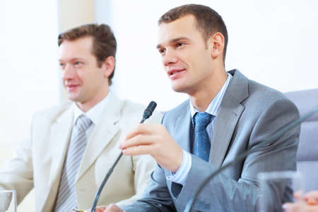 Image of two businesspeople sitting at table at conference speaking in microphone photo