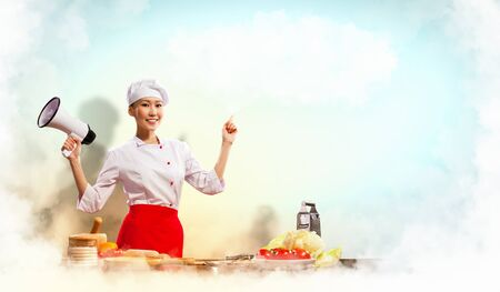 Asian female cook holding megaphone with space for text Stock Photo - 17494290