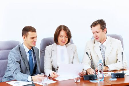 Image of three businesspeople sitting at table at conference Stock Photo - 17494667