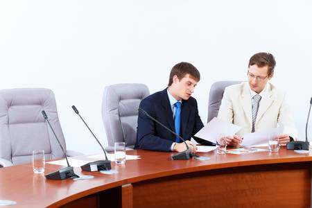Image of two businessmen sitting at table at conference Stock Photo - 17494620