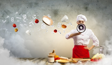 Asian female cook holding megaphone vegetables flying in air Stock Photo - 17494675