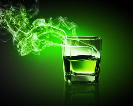 going out: Glass of green absinth with fume going out