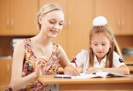 Young female teacher working with children at school Stock Photo - 17494648