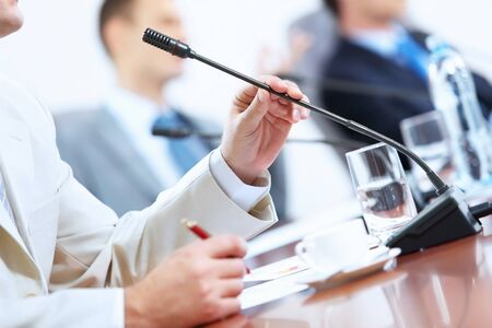 Image of businessman s hands holding microphone at conference photo