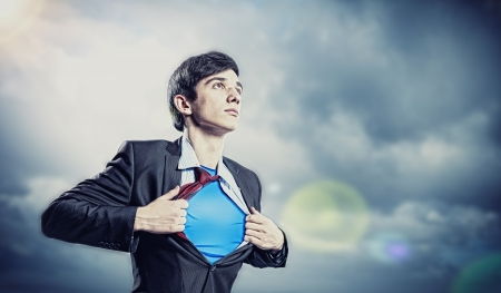 Image of young businessman showing superhero suit underneath his shirt photo