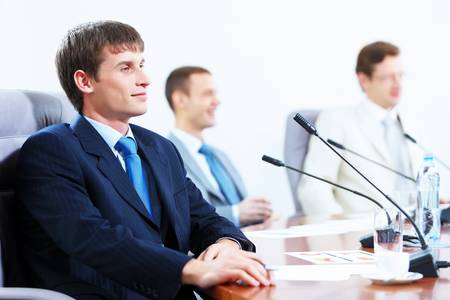 Image of three businesspeople at table at conference Stock Photo - 17494627