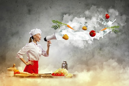 Asian female cook holding megaphone vegetables flying in air Stock Photo - 17494711