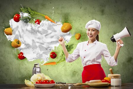 Asian female cook holding megaphone vegetables flying in air Stock Photo - 17494708