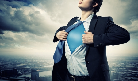 business costume: Image of young businessman showing superhero suit underneath his shirt standing against city background Stock Photo