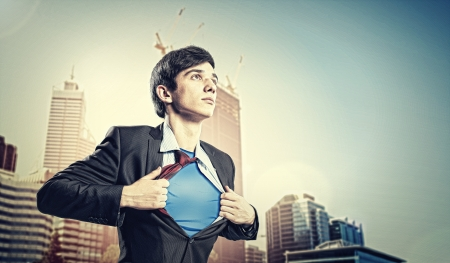 Image of young businessman showing superhero suit underneath his shirt standing against city background photo