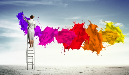 color mixing: Young woman standing on ladder drawing splashes with finger Stock Photo
