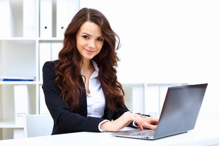 ビジネス: 若いきれいなオフィスでノートを持つ女性実業家