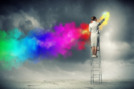 Young woman standing on ladder drawing splashes with finger photo